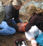 Wilderness First Responder student applying an improvised cervical collar to a trauma patient.